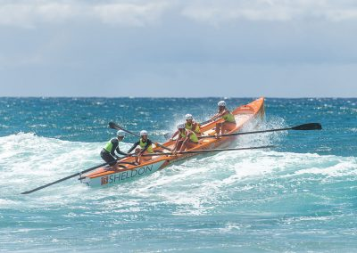surf boat rowing team in big waves